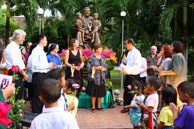Die Gäste und die vielen Kinder versammeln sich vor dem Denkmal von Vater Ray im Waisenhaus.