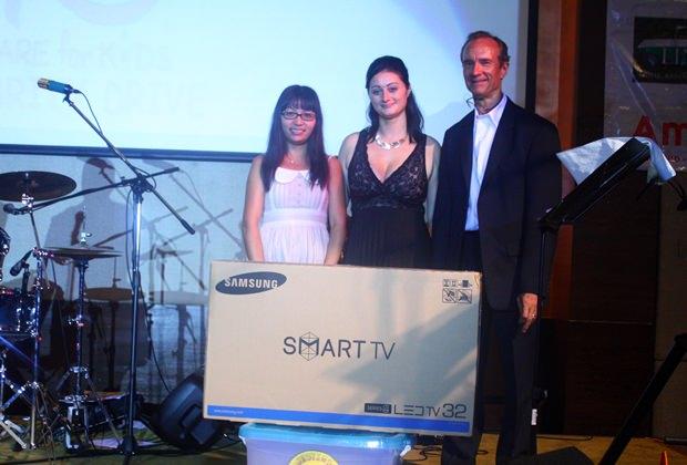 """(von links) Ja gewinnt den Samsung 32"""" Flach-TV. Deborah Philbrook und Lewis Woody Underwood überreichen den Preis."""