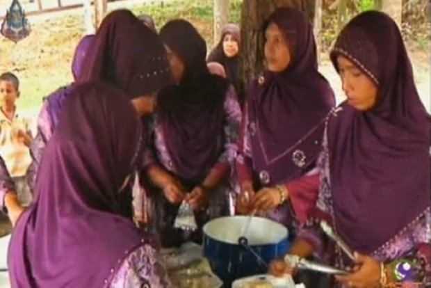 Die Frauen sitzen zusammen und bereiten gemeinsam das Essen zu.