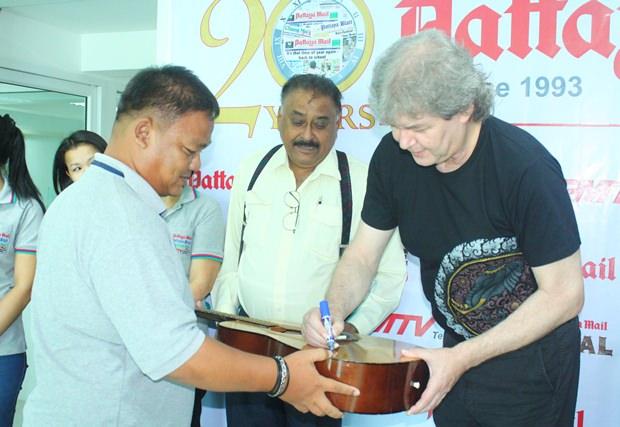 """Hucky signiert die Gitarre vom Leiter der Graphik-Abteilung von Pattaya Mail, Thanawat """"King"""" Suansuk."""