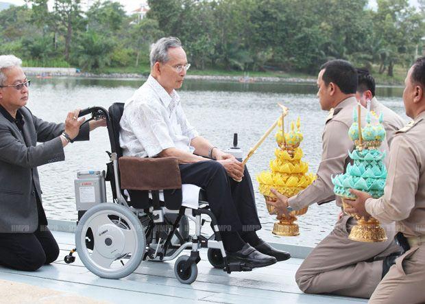 Der König entzündet die Räucherstäbchen auf seinem Krathong. (Photo mit Erlaubnis vom Königlichen Haushalt).