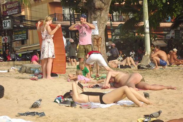 Ausländische Touristen aalen sich am Strand.