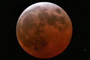 Die Erde schimmert kupferrot bei einer totalen Mondfinsternis