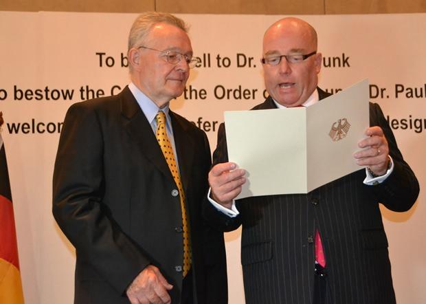 Seine Exzellenz Botschafter Rolf Schulze (rechts) liest dem scheidenden deutschen Honorarkonsul Dr. Paul Strunk einen Brief des deutschen Bundespräsidenten Joachim Gauck vor, in dem dieser ihn als Träger des Bundesverdienstkreuzes am Band beglückwünscht.