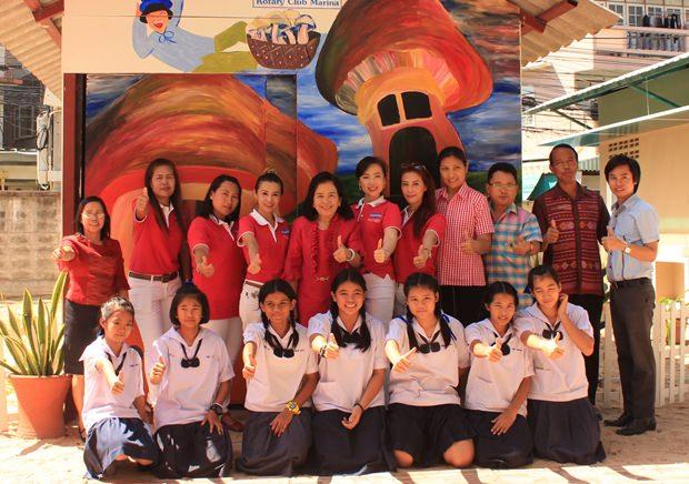 Einige Mitglieder des YWCA übergeben eine neue Pilzzucht-Hütte an die Schule Nr. 8.