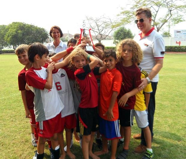 Die Schweizer Botschafterin Christine Schraner-Burgener (im Hintergrund) mit dem siegreichen Kinderteam nach der Übergabe des Pokals.
