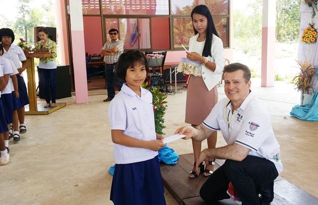 Dr. Ramin übergibt hier einem kleinen Mädchen das Schulgeld. Insgesamt machte er dies 50 Mal.