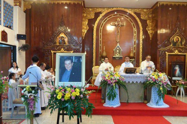 Die heilige Messe wird von Vater Peter, dem Präsidenten der Father Ray Foundation gelesen. Im Vordergrund ein Bildnis von Vater Ray Brennan.
