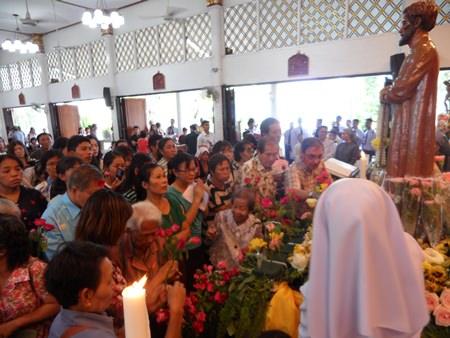 Der Bischof und die Gläubigern legen Rosen zu Füßen des Heiligen Nikolaus nieder.