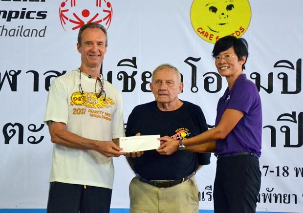 Lewis Underwood gibt im Namen von Jester's Care for Kids einen Scheck über 150.000 Baht.