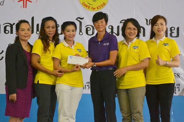 Praichit Jetapai vom YWCA hilft mit einem 15.000 Baht Scheck.