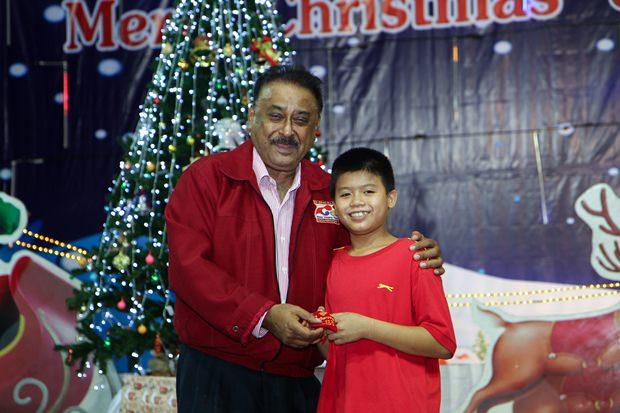 Peter Malhotra überreicht dem kleinen Jungen den Hauptpreis: eine Goldkette.