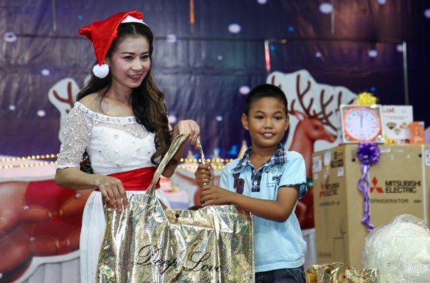 YWCA Präsidentin Praichit Jetapai freut sich bei der Geschenkübergabe mit den Kindern.