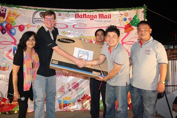 Amnart Kankamjud von der Grafik Abteilung der Pattaya Mail gewinnt den 32 inch großen Flachbildschirm-Fernseher und Jan Olav Aamlid übergibt ihm diesen, Mit ins foto reingestellt haben sich Sue (links) und King.