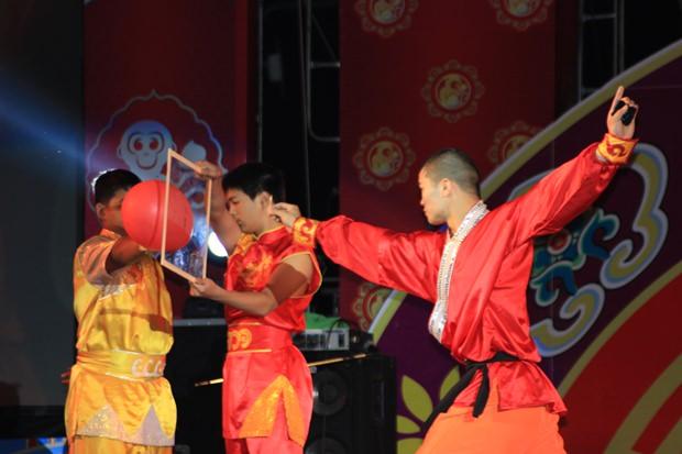 Ein Darsteller von Bangkoks Jaow Poh Jiew, Thee Eiy, begeistert die Zuschauer indem er einen Pfeil durch Glas schießt und damit einen Ballon platzen lässt.