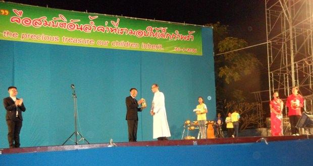 Veerasilapha Tarasilapha (Mitte) erhält ein Geschenk von Direktor Vater Michael Weera Panrak, während der MC des Event, Vater John Nuphan Thasmalee (links) applaudiert.
