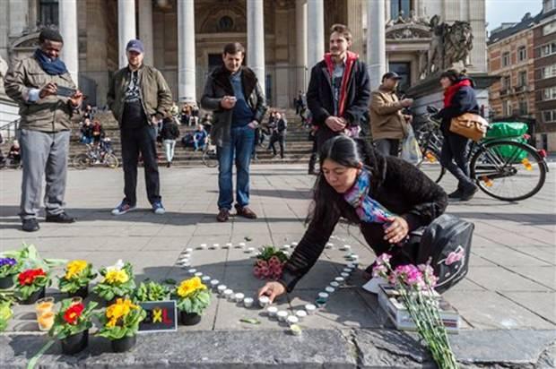 Während die Suche nach dem flüchtigen Terroristen weitergeht, legen Menschen auf dem Schauplatz des grausigen Geschehens Blumen nieder.