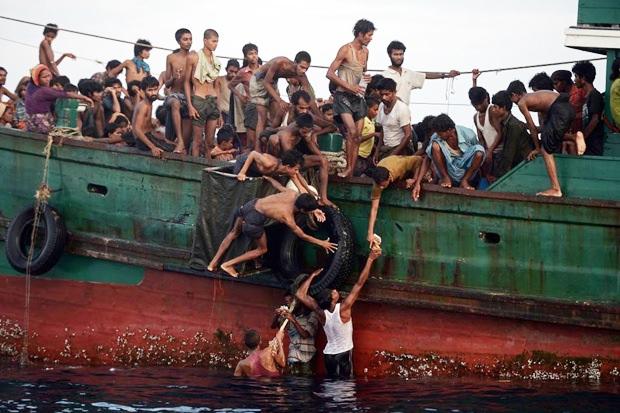 Flüchtlinge die von Schleppern nach Thailand geführt wurden, versuchen an Land zu kommen.
