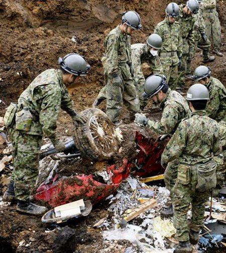 Soldaten graben ein Auto aus den Erdmassen, da durch das Beben ein starker Erdrutsch entstanden war. (Takuya Inaba/Kyodo News via AP)
