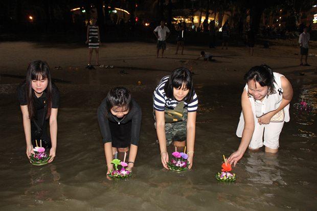 Familien lassen ihre Krathongs gemeinsam zu Wasser am Pattaya Strand.