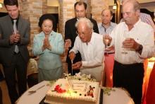 Franz Ackermann (Mitte) schneidet seine Geburtstagstorte in Gegenwart von Panga Vathanakul (2. von links), Prem Calais (3. von links) und Thibault Sellier (ganz links), sowie Freunden, an.
