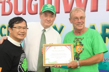 Steve Devereux (rechts) erhält aus den Händen von Botschafter Rogers (Mitte) und Vater Michael (links) eine Auszeichnung.