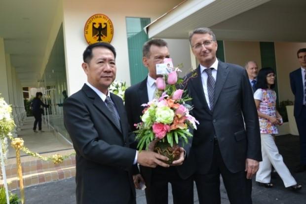 Bezirkshauptmann Naris Miramaiwong gibt Rudolf Hofer und Botschafter Peter Prügel einen Blumenkorb zur Eröffnung.