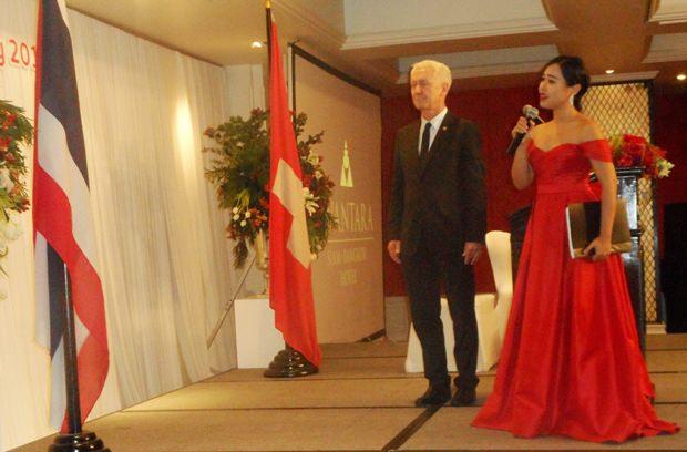 Botschafter Ivo Sieber steht vor der thailändischen Flagge während Pimluk die Hymne singt.