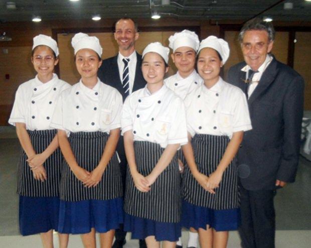 Die jungen Kochschülerinnen strahlen mit Jan Scheer und Axel Brauer um die Wette.