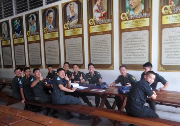 Studenten sitzen beim Lernen nach dem Mittagessen unter den Bildern von König Rama IX.