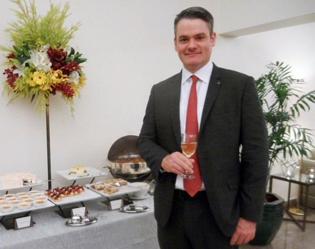 Sukothai Generalmanager Thomas Schmitt-Gläser steht beim Süßigkeiten Stand.
