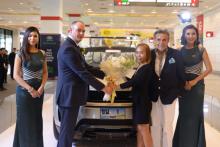 (Von links) Jack Salsbury, der Generalmanager von Range Rover übergibt einen Blumenstrauß an Bo während Axel stolz zusieht.