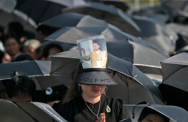 Trauernde sprechen Gebete und trotzen unter schwarzen Schirmen dem Regen. (AP Photo/Wason Wanichakorn)