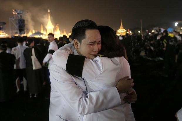 Thailändische Beamte umarmen sich in Trauer als der Rauch aus dem crematorium hochsteigt. (AP Photo/Wason Wanichakorn)