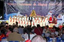 Der Kinderchor des Pattaya Orphanage singt Weihnachtslieder, geleitet von Direktor Vater Michael Weera (Mitte) und Radchada Chomjinda (neben dem Weihnachtsmann rechts).