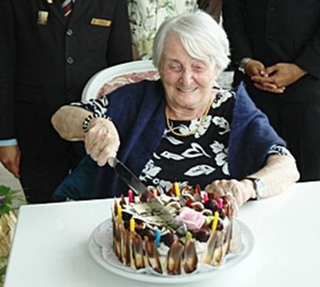 Herta schneidet fröhlich die Geburtstagstorte zu ihrem 99. Geburtstag an.