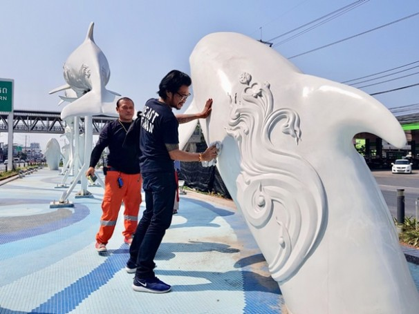 Arbeiter entfernen die aufgesprühte Farbe von Pattayas Wahrzeichen.