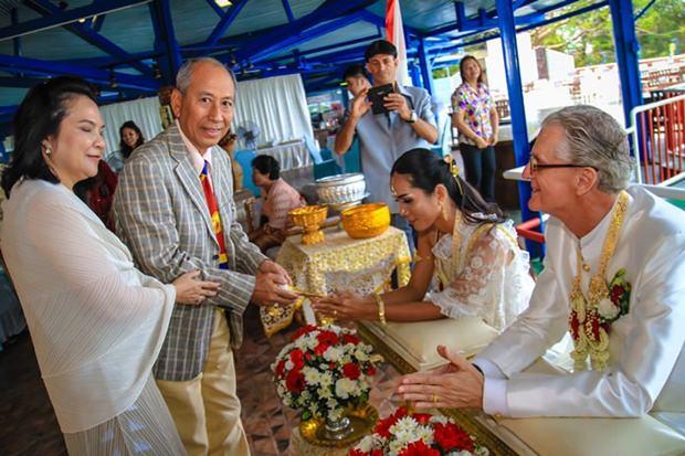 Klisada Eineew und Kanjana geben geweihtes Wasser über die Hände des Brautpaares in Verbindung mit den besten Wünschen fuer deren Zukunft.