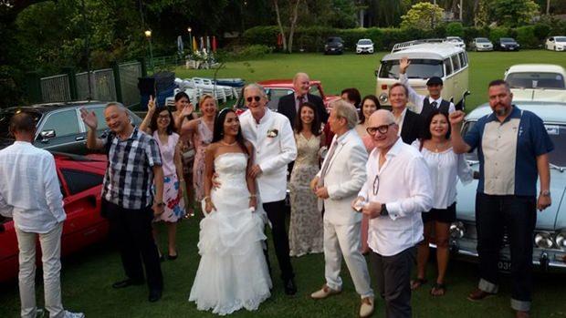 Oldtimer-Freunde vor Ihren Autos begrüssen das Brautpaar.