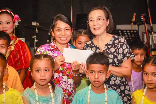 Präsident Nachlada Nammontree überreicht Radchada Chomjinda eine Spende für die Kinder.