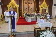 Pater Philip spricht Gebete neben der Asche des Verstorbenen.