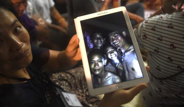 Glückliche Angehörigen zeigen ein Bild aus der Höhle von den Kindern und ihrem Trainer. Das Foto wurde von Einsatzkräften aufgenommen. (Bild: AP)
