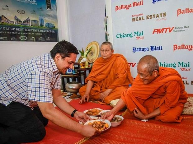 Prince Malhotra, der stellvertretende MD reicht den Mönchen nach den Gebeten das Essen.