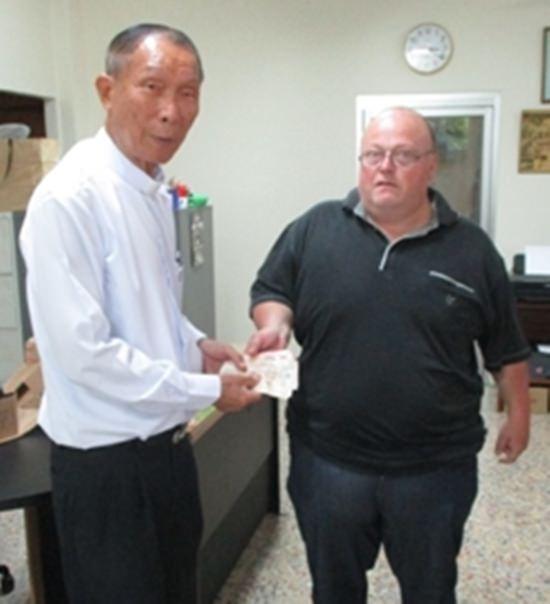 Martin Jahraus (rechts) übergibt 5.500 Baht an Vater Michael Weera.