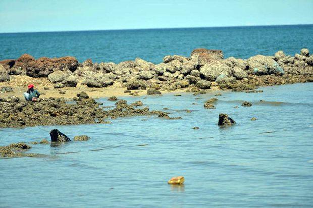 Zuständige Beamte untersuchen die Abflussrohre die am Wongamat Strand ins Meer führen.
