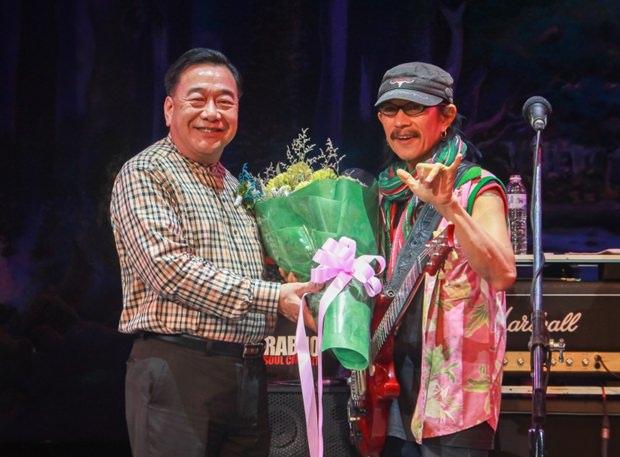 Vizegouverneur Phawat Lertmukhda, überreicht Aed Carabao einen Blumenstrauß.
