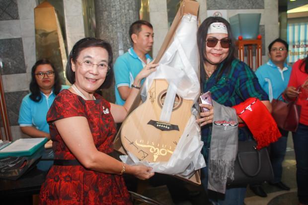 Rachada Chomjinda überreicht einem der glücklichen Bieter eine ersteigerte Carabao Gitarre.
