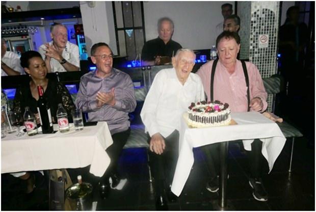 Archie (Mitte) herhält Applaus nachdem er die Kerzen auf seiner Geburtstagstorte ausgeblasen hat. (Von links) Carol und Geoff Doidge, Archie und Allan Riddel.