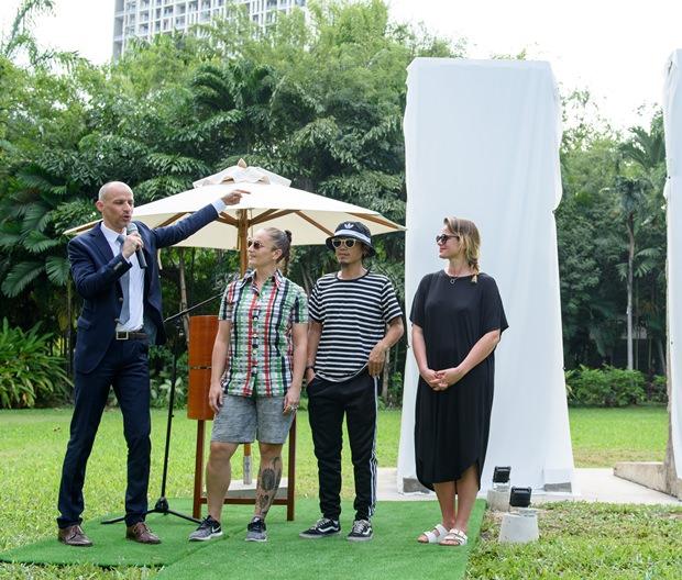 (Jan Scheer außen links) stellt die drei Straßenkünstler vor, die die Mauerfragmente bemalten. Von links: Kashink mit dem Damenbart aus Frankreich, Mue Bon aus Thailand und Julia Benz aus Deutschland.