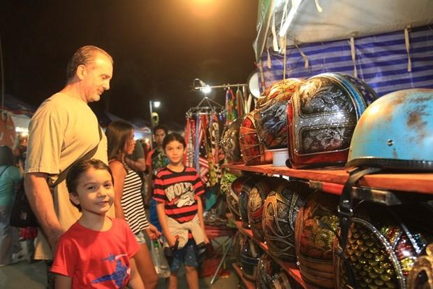 Das Kind will den Vater dazu überreden einmen farbigen Schutzhelm zu kaufen.